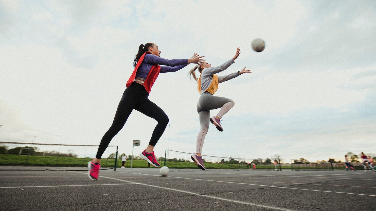 Two women play a game of netball together. They are both wearing sports bibs as one tries to take the netball from the other.
