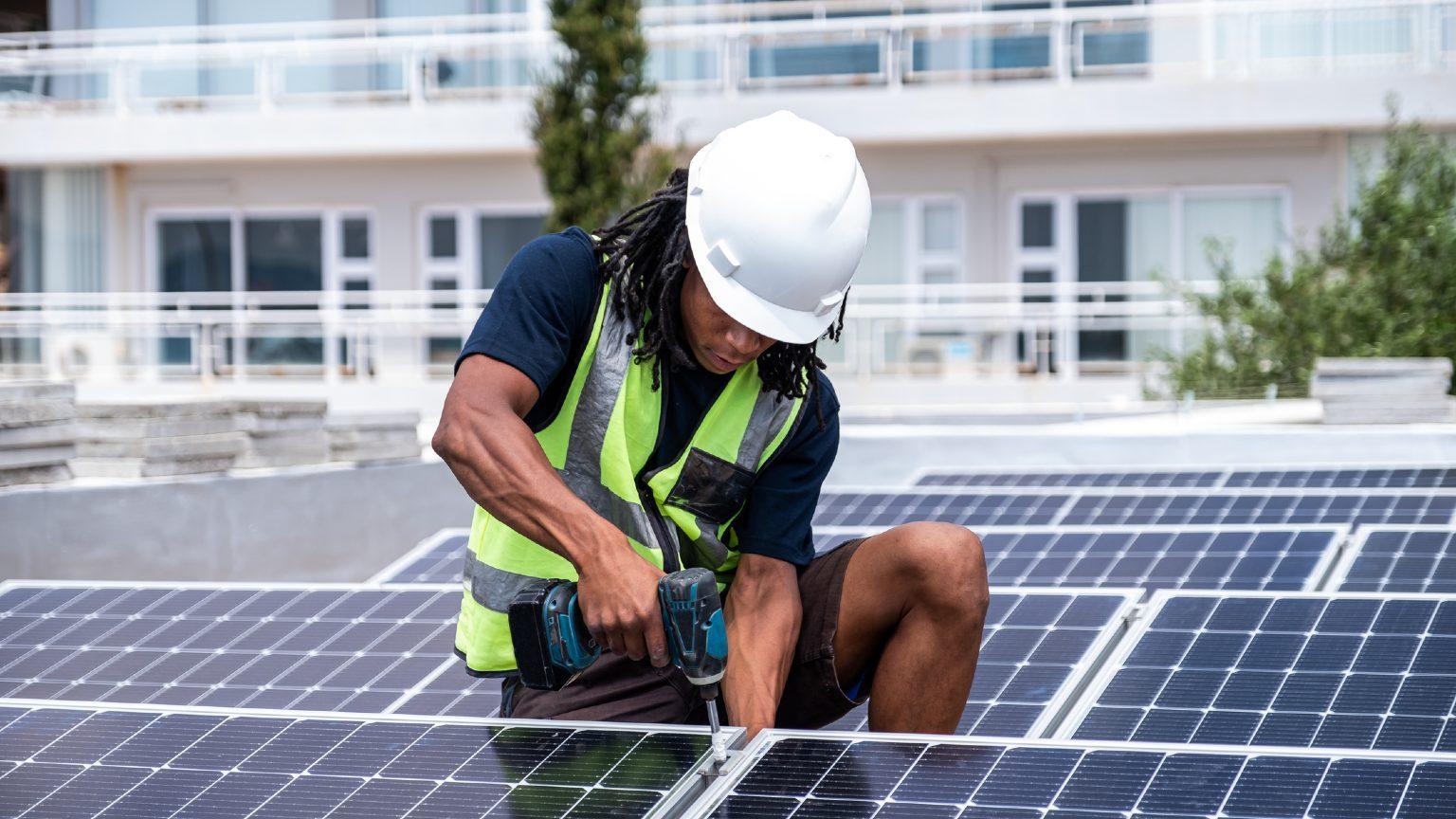 black man installing solar panels