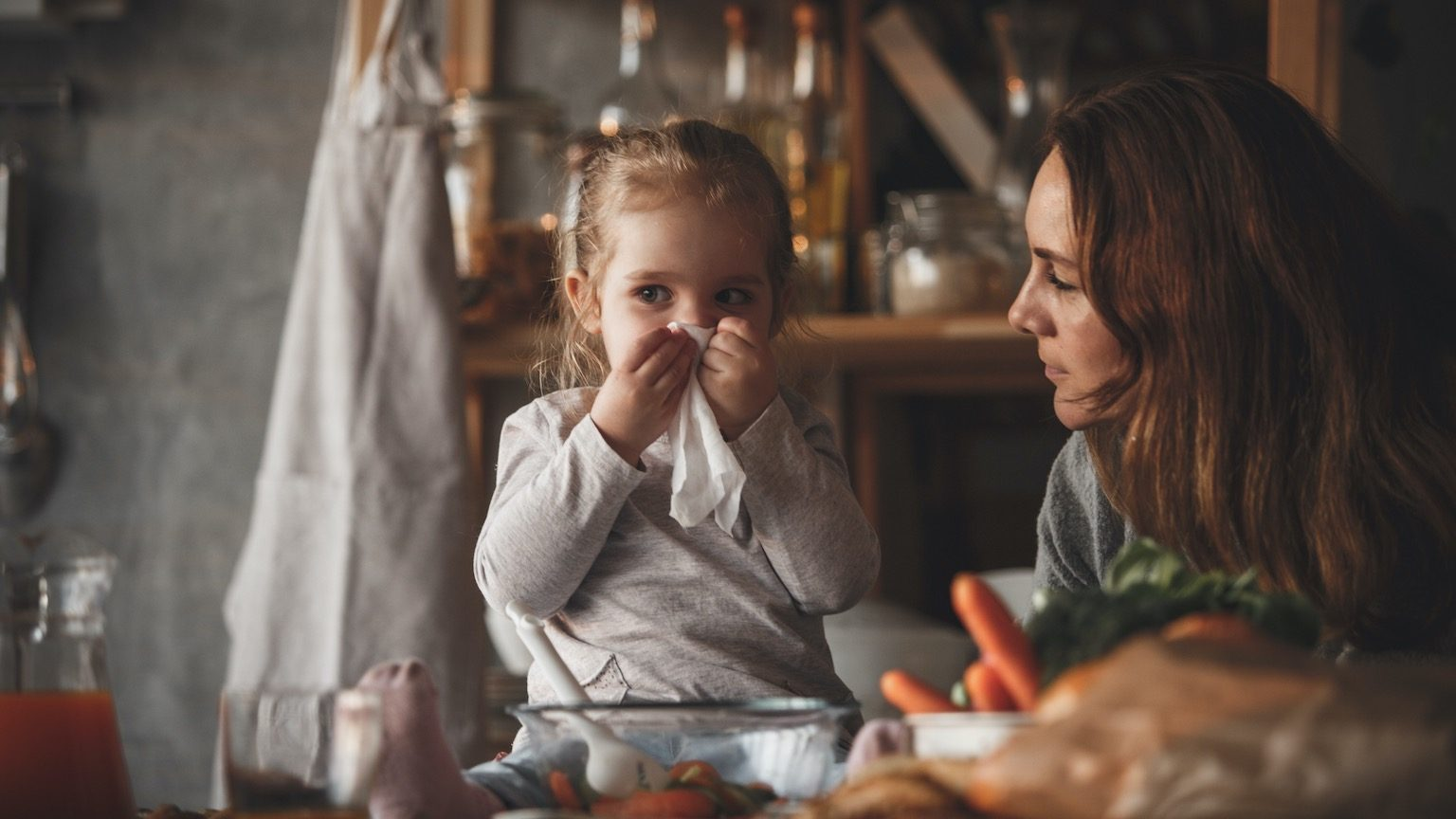 Two year old baby girl wipes her nose with a handkerchief while sitting on the kitchen counter. She is helping her mother preparing vegetables salad.