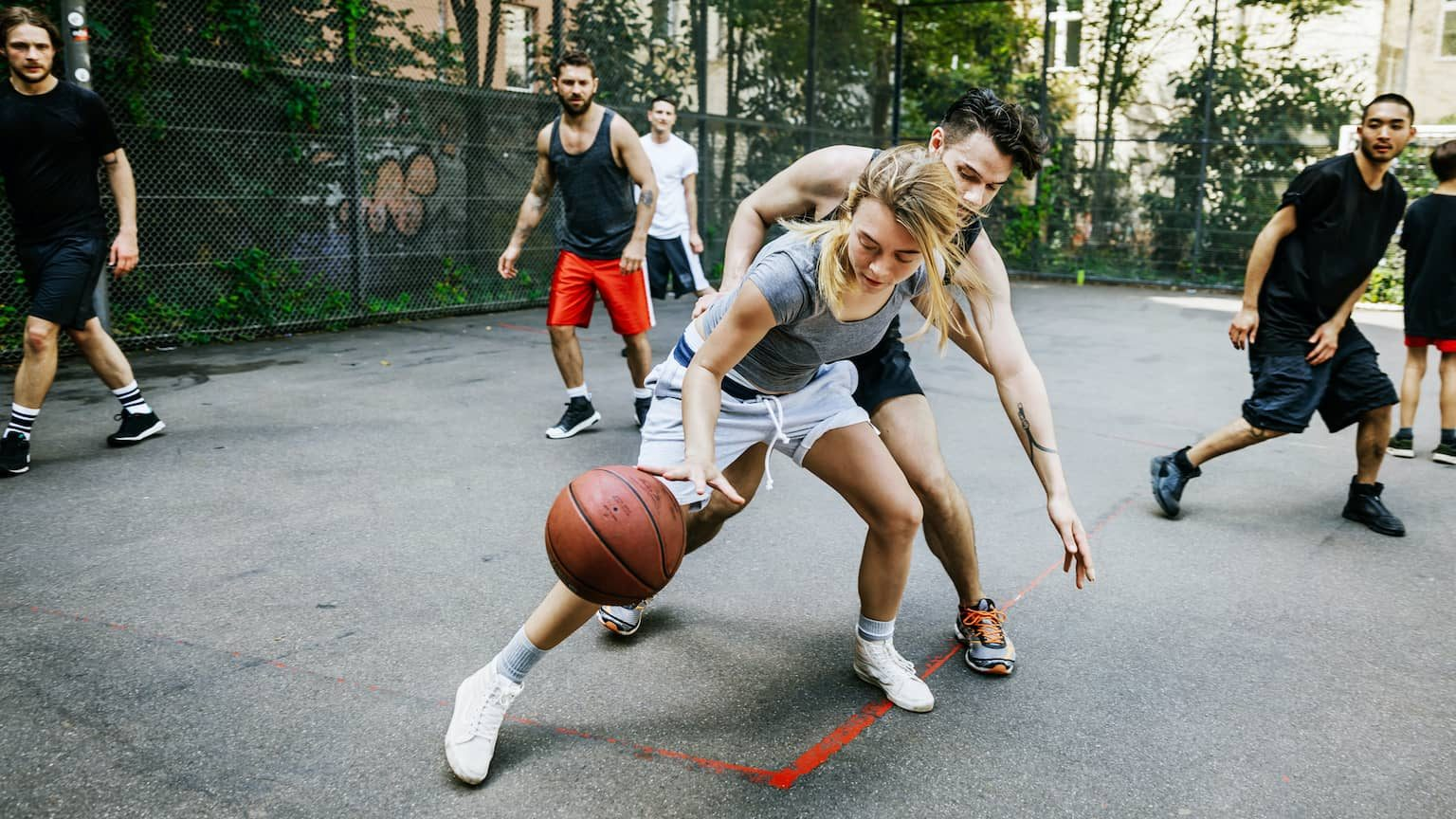 An amateur athlete is skillfully defending her position during a friendly outdoor basketball game in the city.