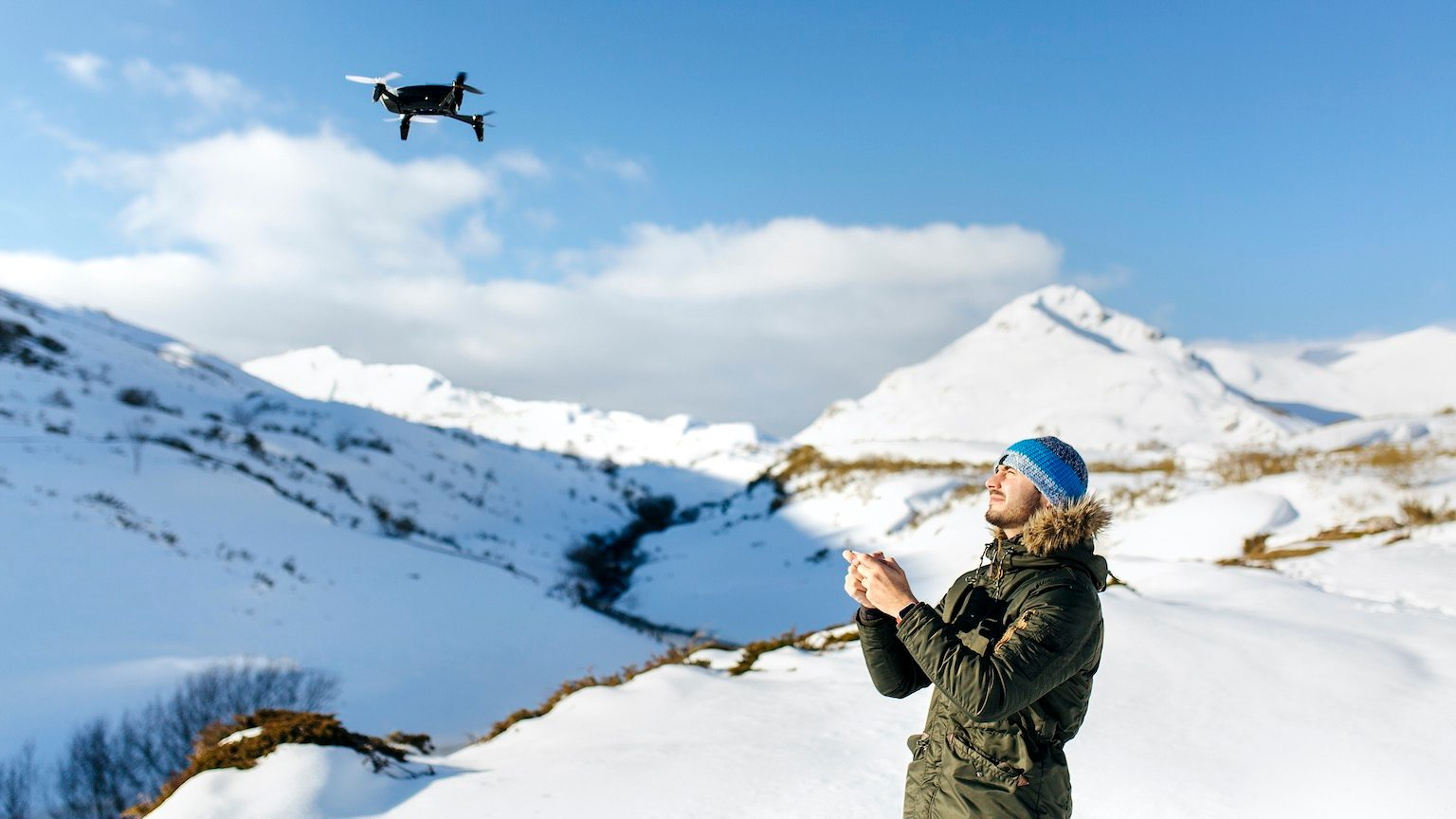 Asturias, Spain, young man driving a drone in a snowy mountains
