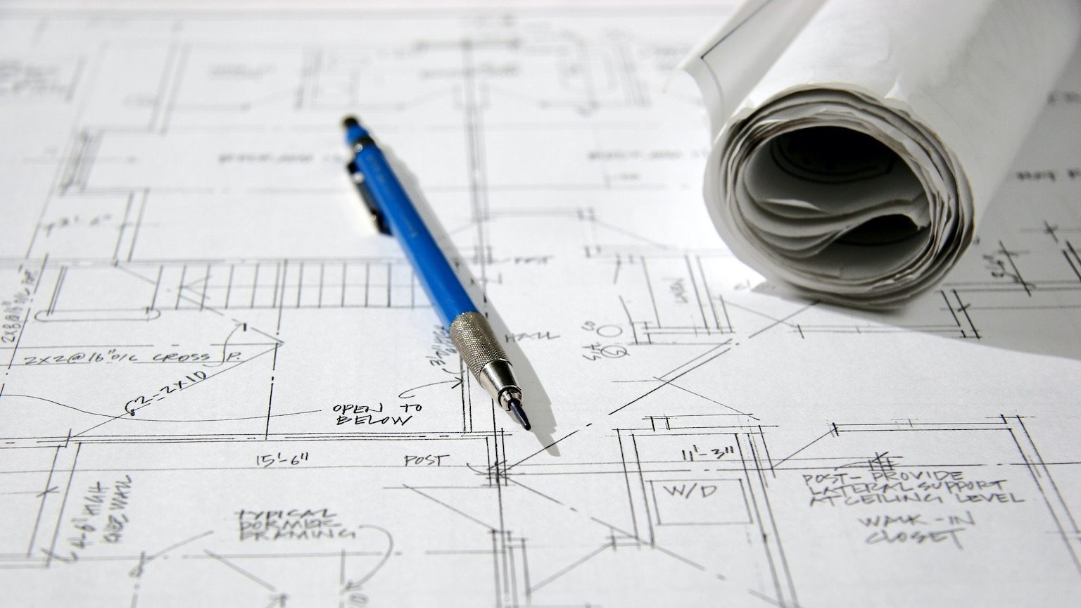 This is a photo of a mechanical pencil and a rolled up blueprint laying on top of an architectural drawing