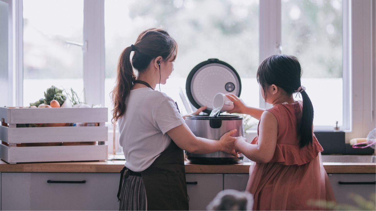 mother cooking preparing food at kitchen with her daughter
