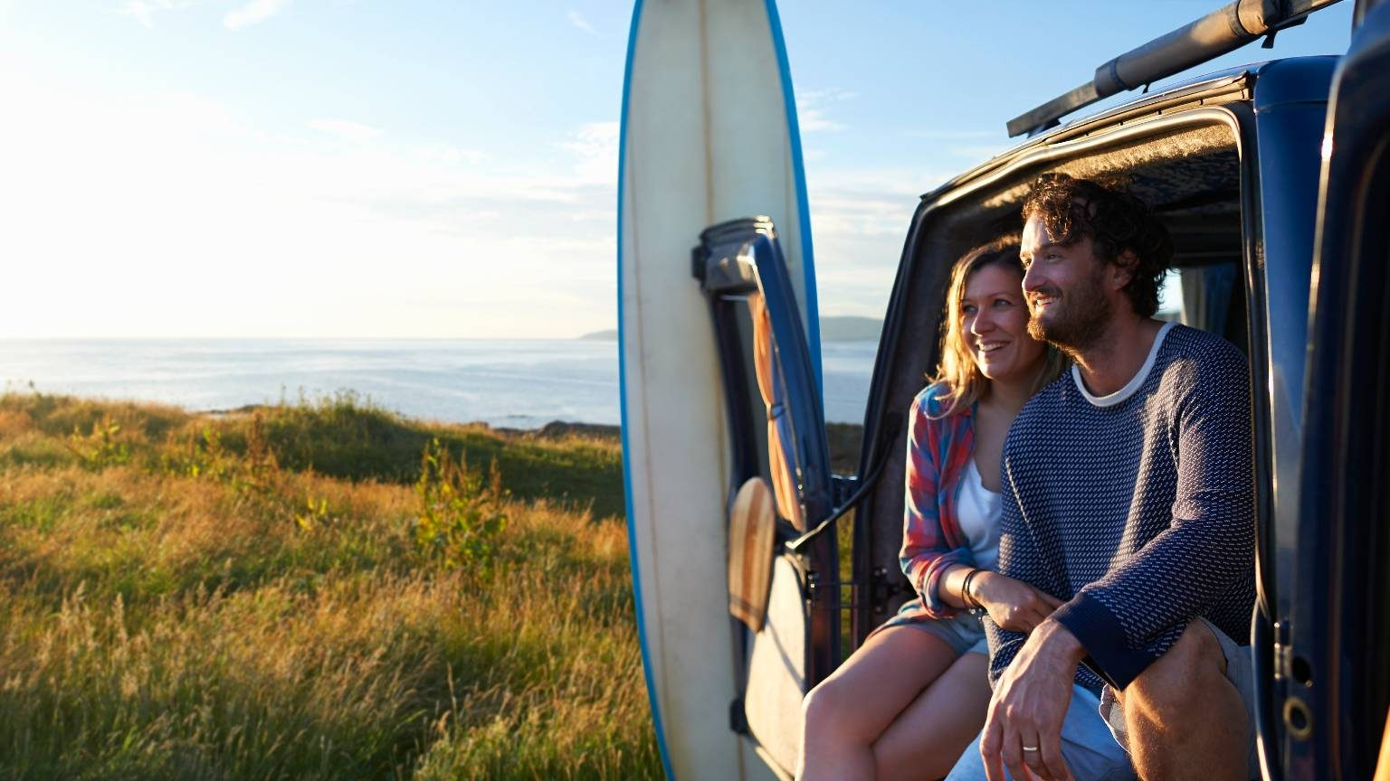 A surfing couple smile as they sit in their camper van and embrace on an idyllic summer Atlantic coastline.