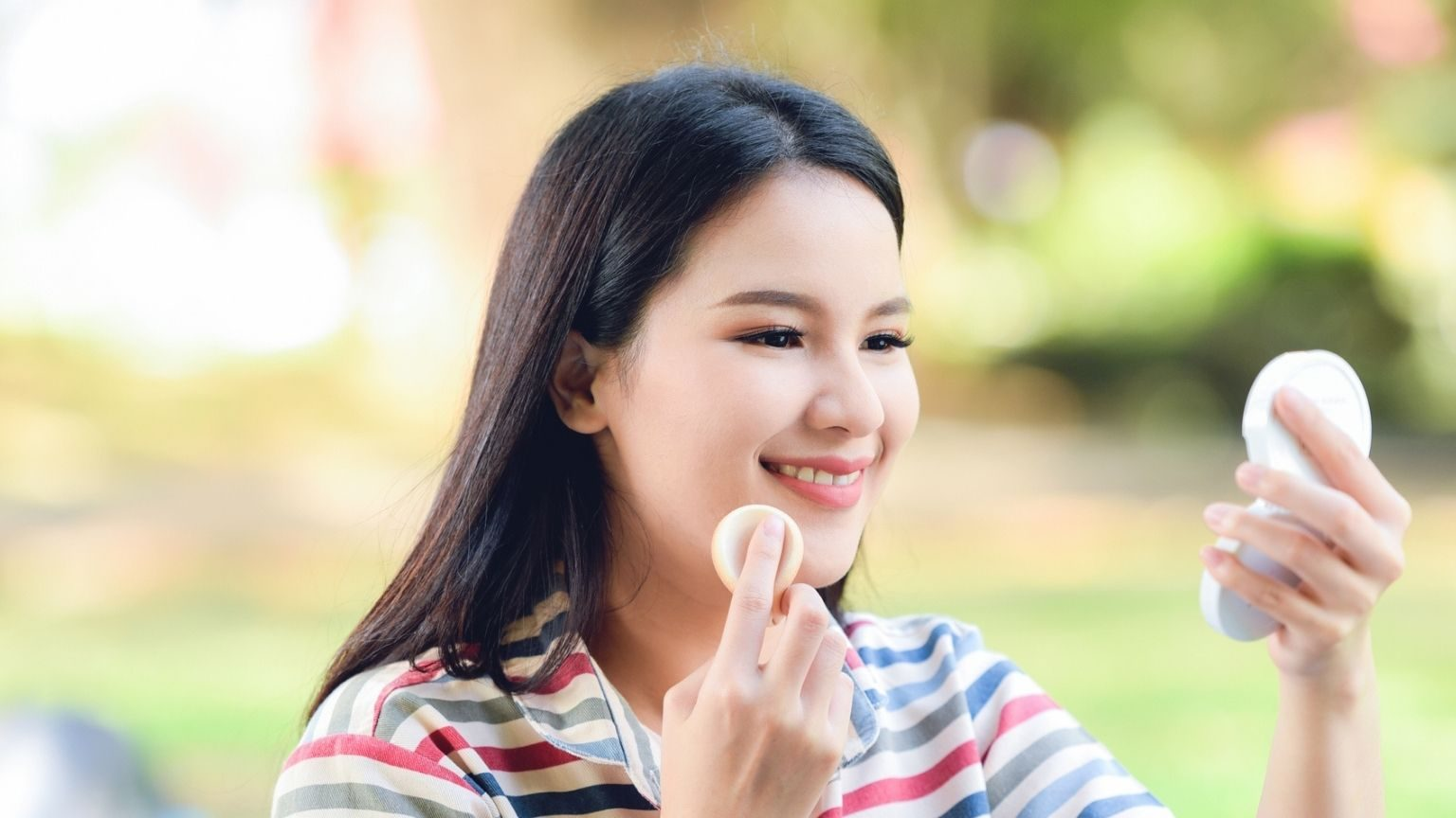 Smiling Woman Applying Make-Up In Park