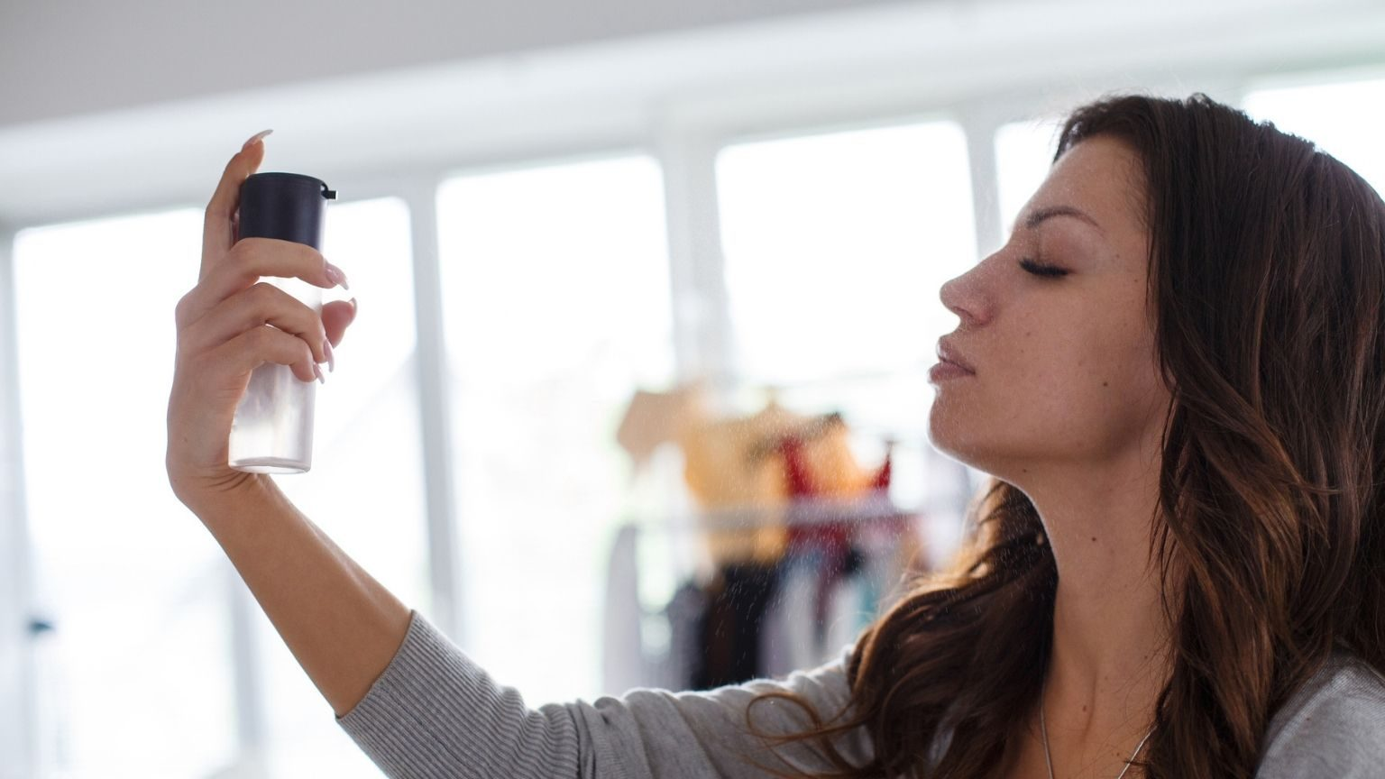 Young woman using setting spray before applying make-up