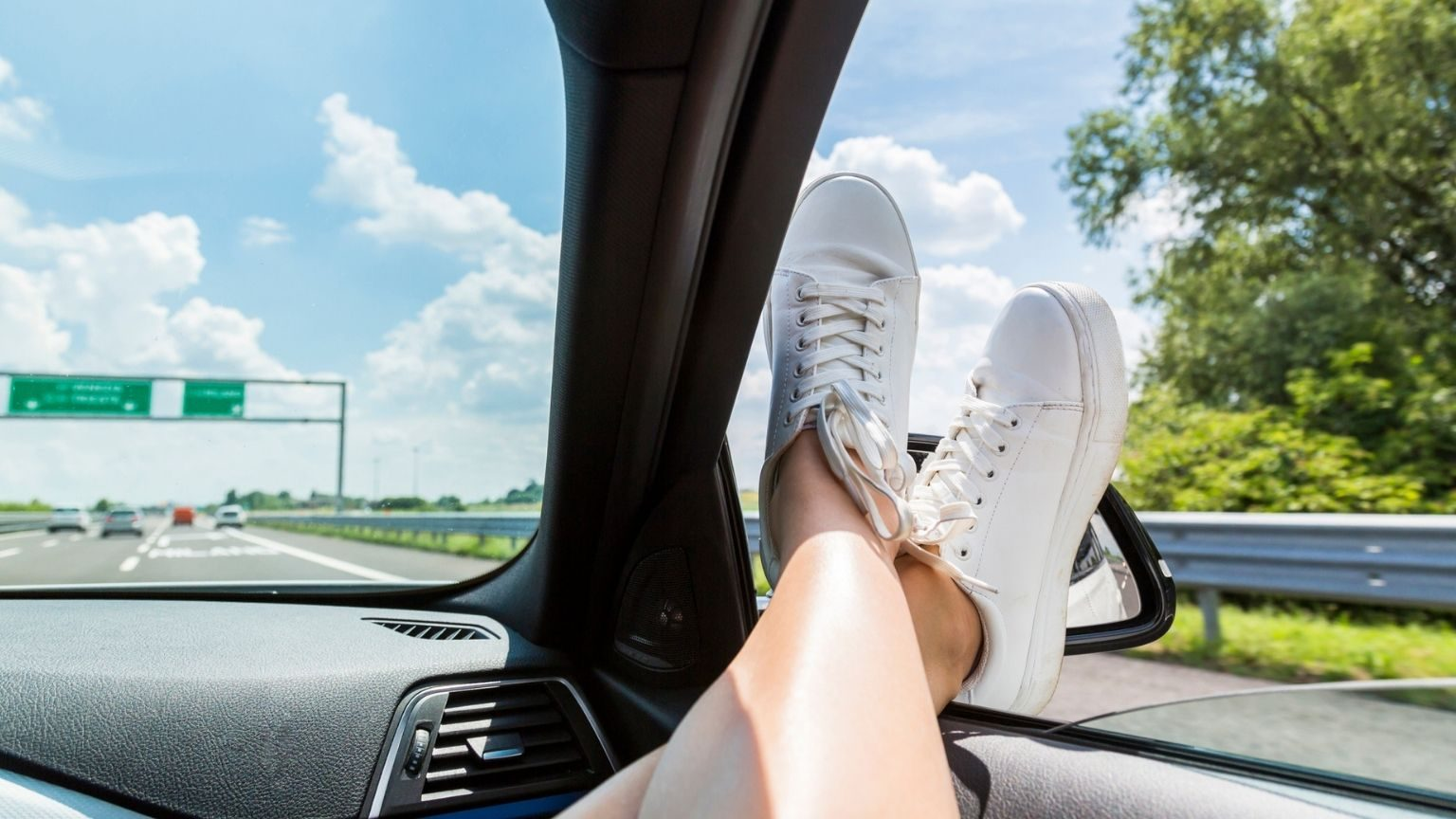 feet of woman leaning out of car window