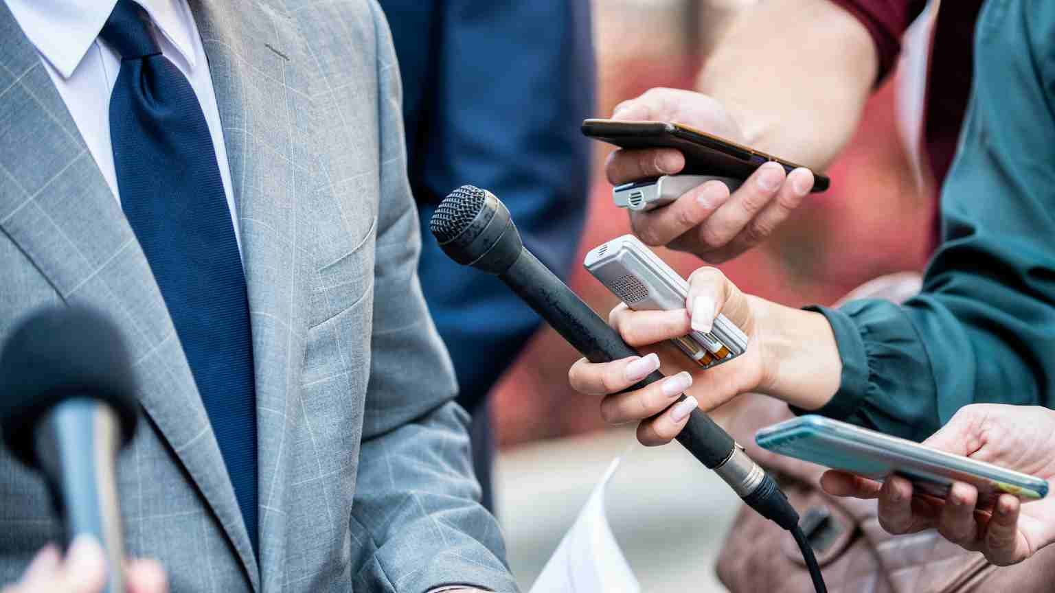 man surrounded by journalists