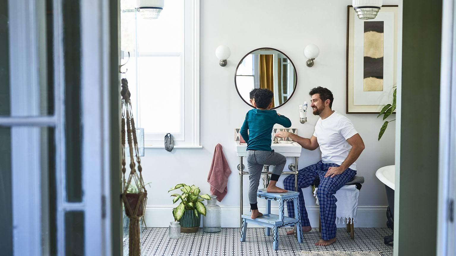 Father helping son brushing teeth