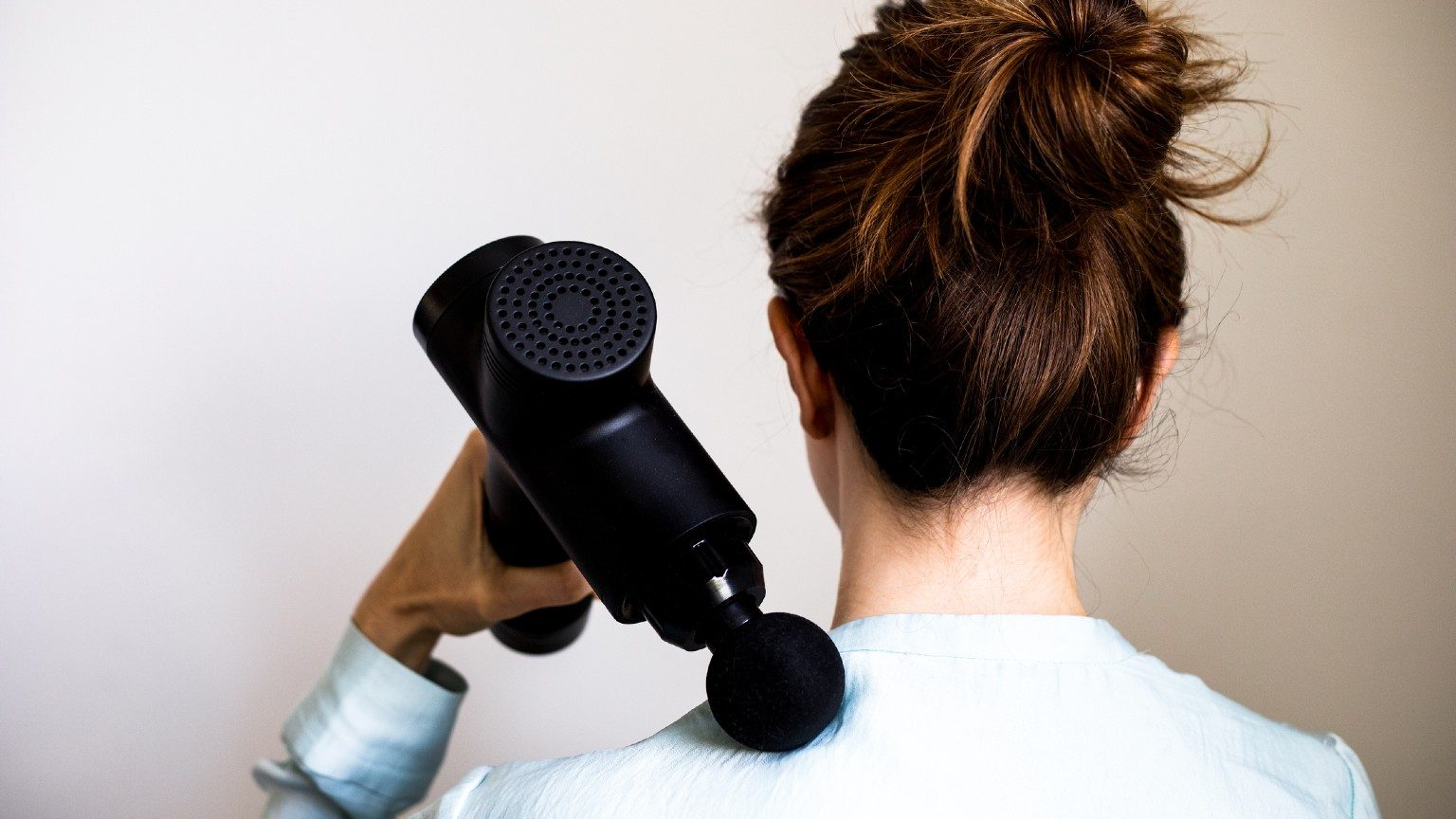 woman using a massage gun