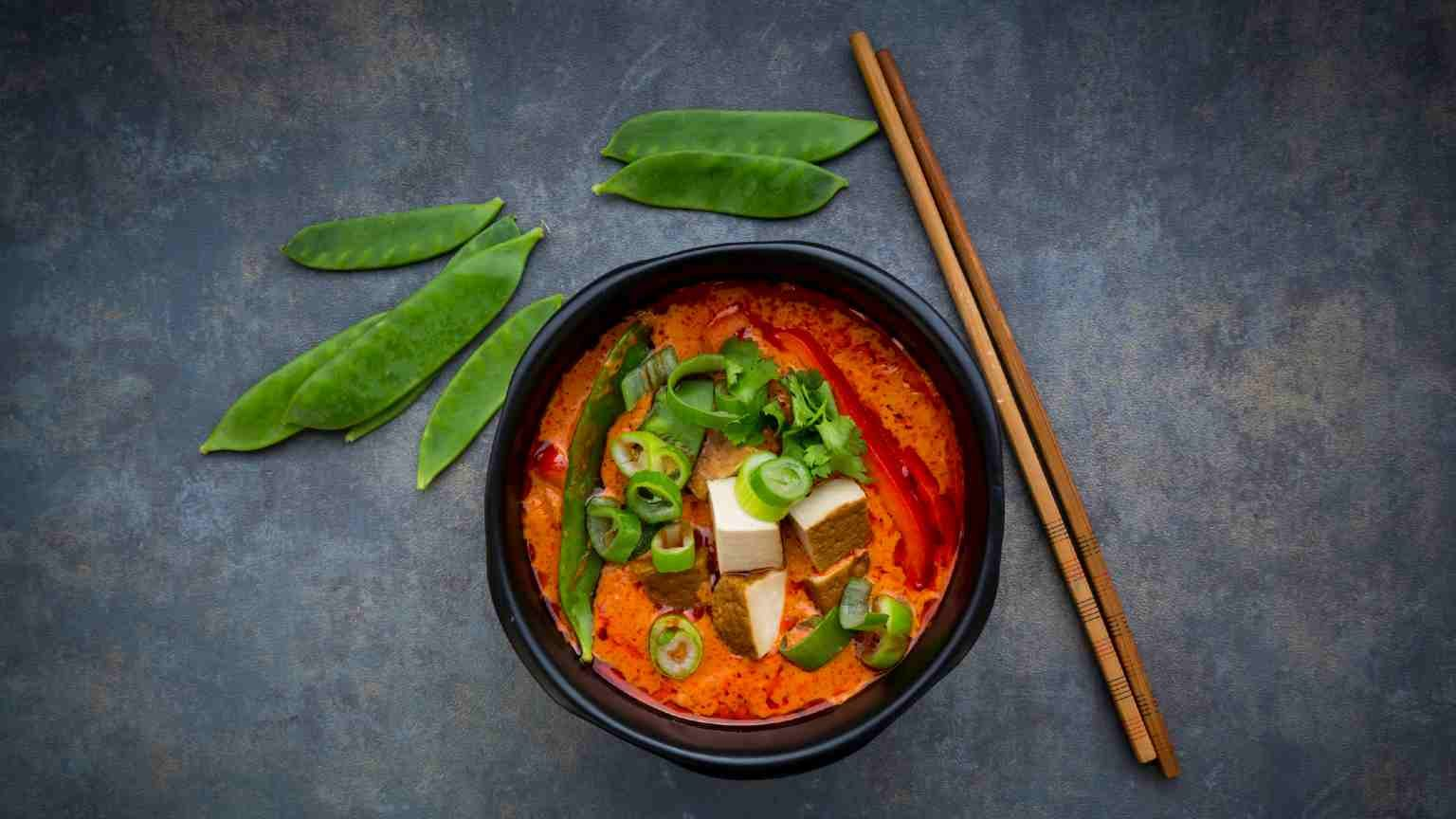 Bowl of red Thai Curry with snow peas, carrots, bell pepper, spring onions and smoked tofu.