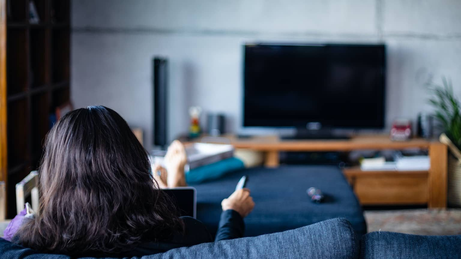 Woman using an air mouse to watch TV