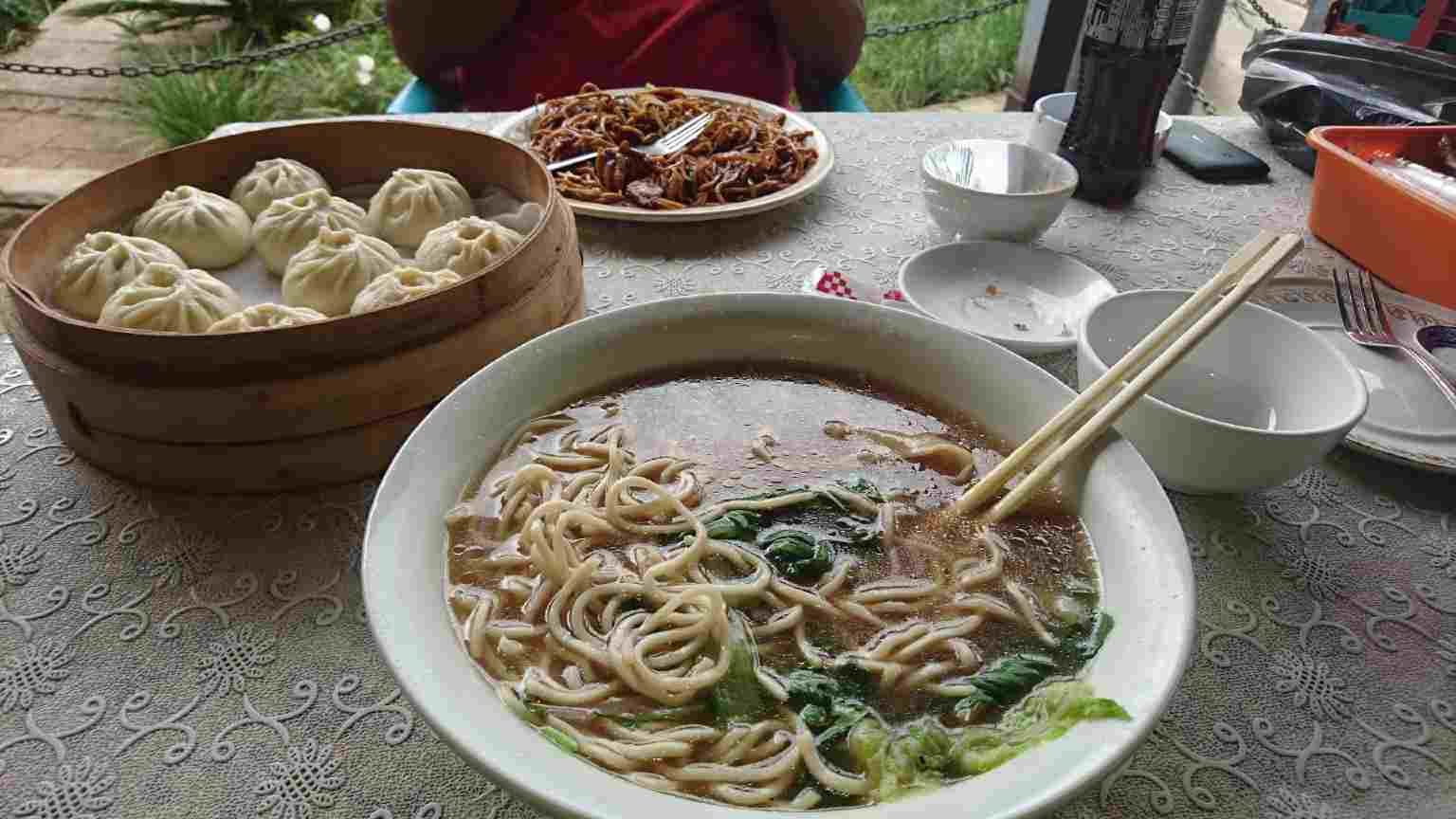 High angle view of noodle soup with Chinese dumplings served on a table.
