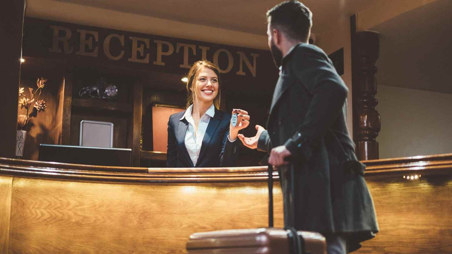 Female receptionist handing a male guest his key