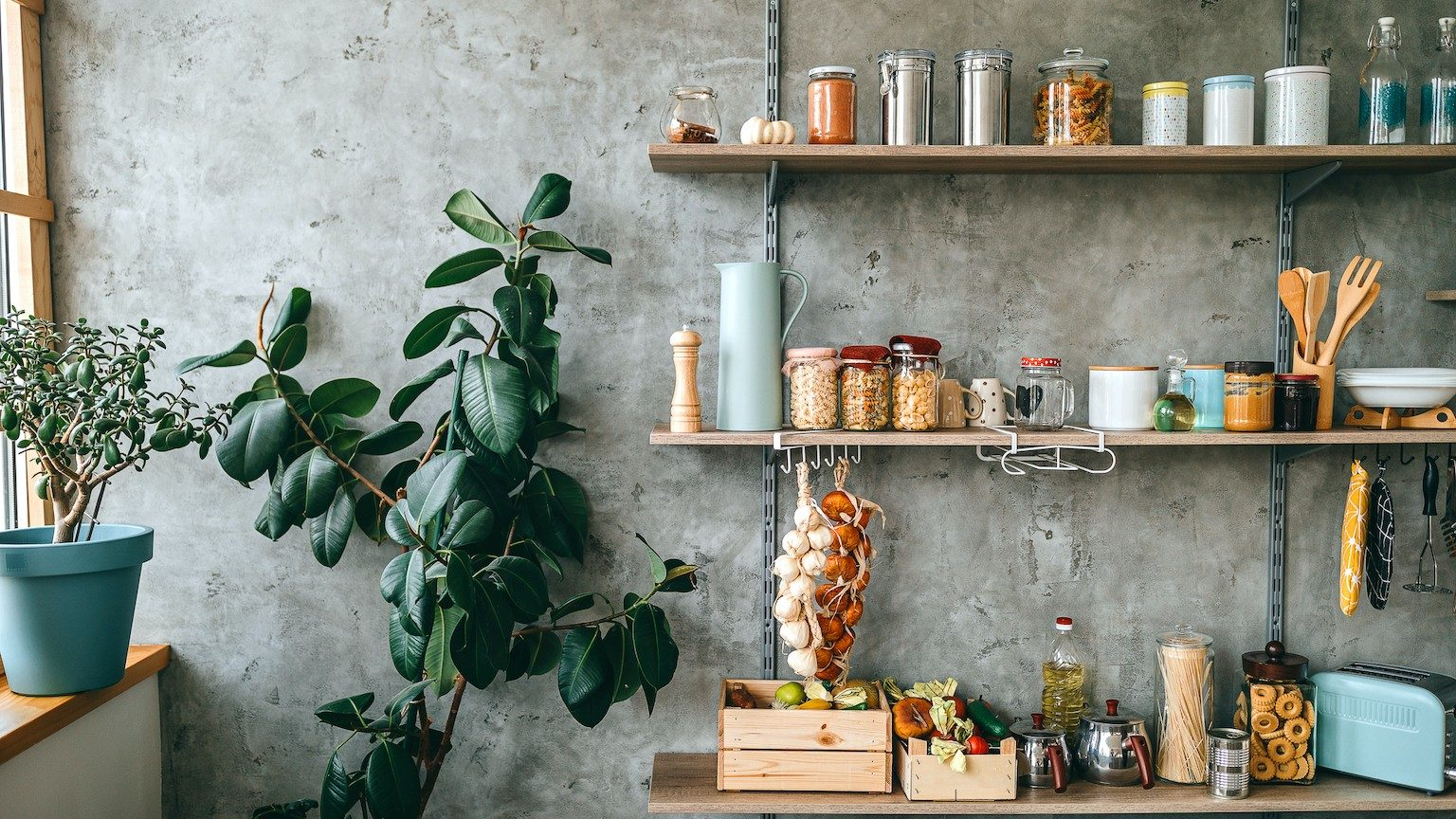 Uncooked groceries in glass jars arranged on wooden shelves of kitchen