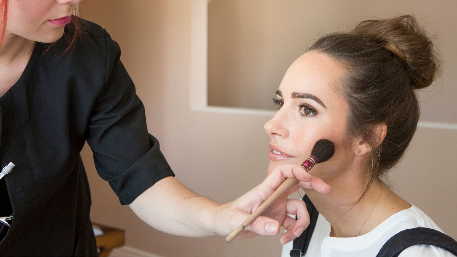 Make up artist applying blusher to female fashion and lifestyle blogger