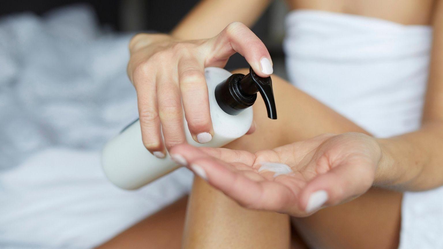 Young woman putting moisturiser