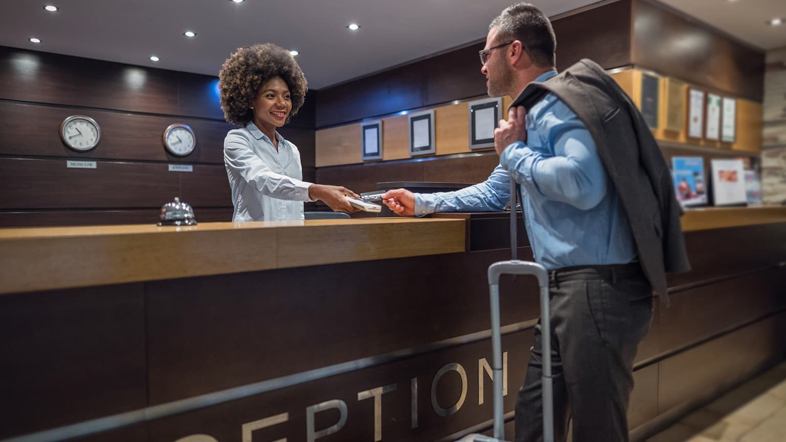 Man checking in at a hotel with a receptionist