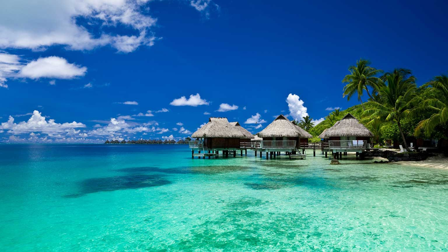 View of several overwater bungalows in Bora Bora with gorgeous sea and sky