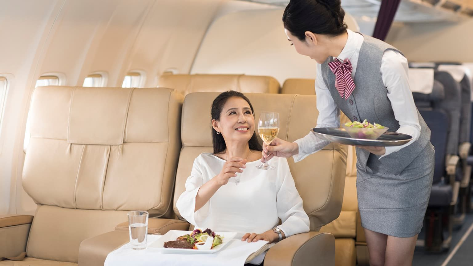 Airline stewardess serving food to passenger