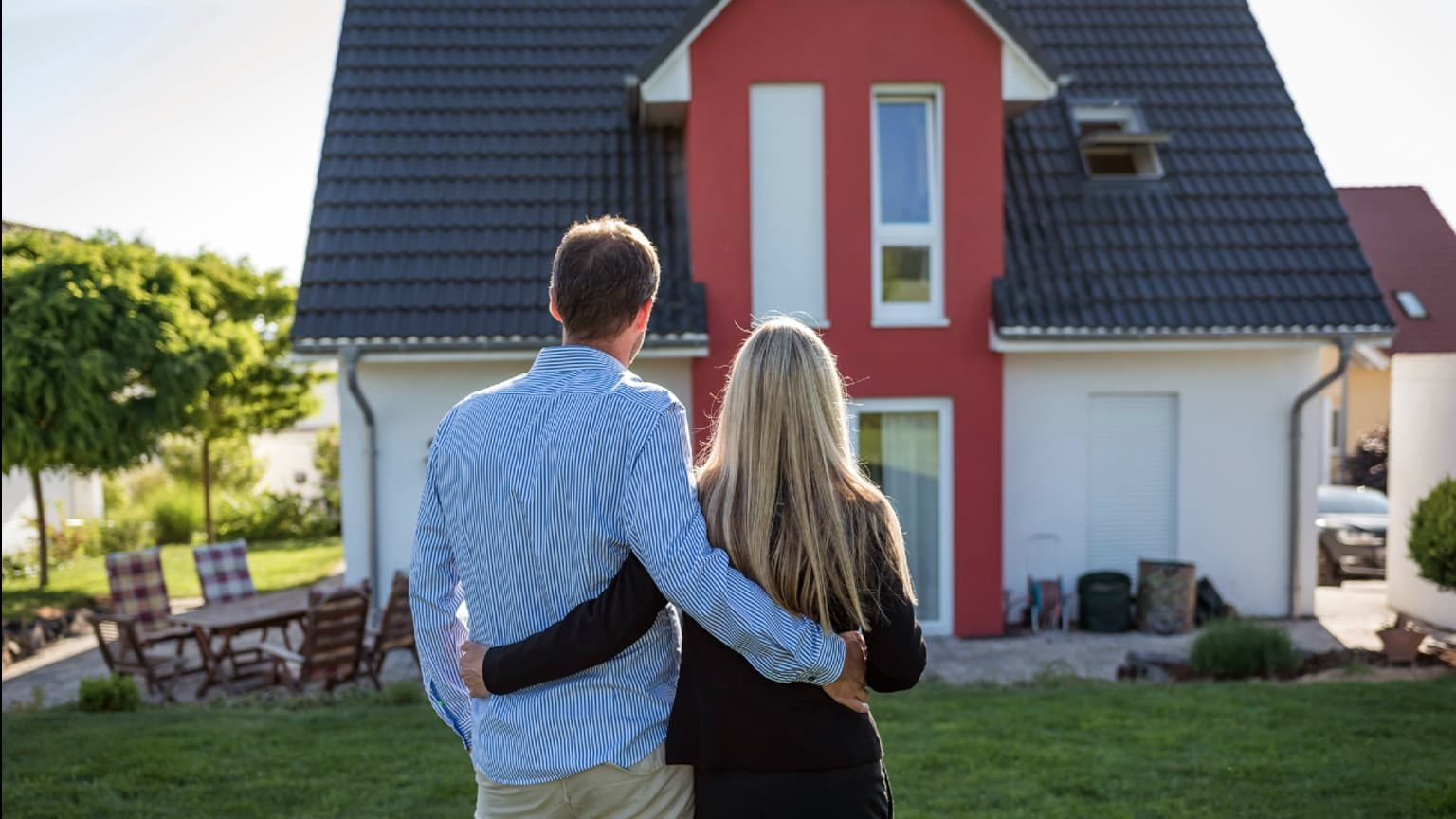 A couple with hands around each other standing in front of a house