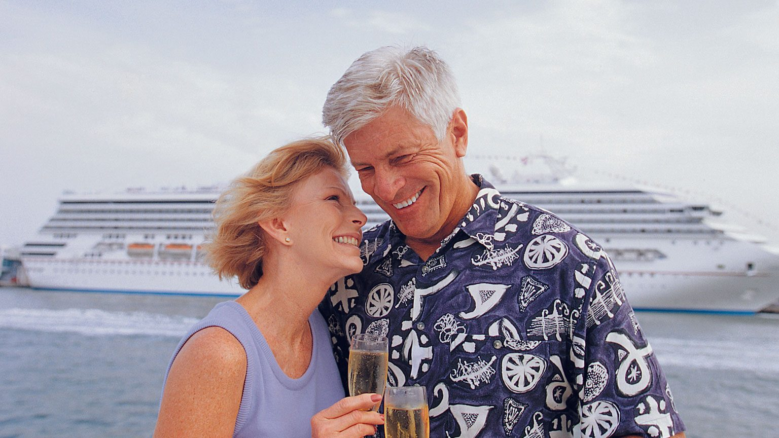 Senior couple smiling and drinking champagne with cruise ship in the background