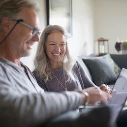 Smiling senior couple using laptop