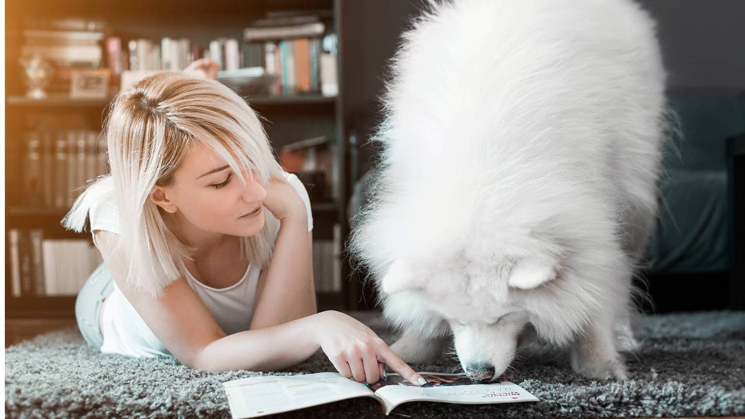 Woman pointing at magazine while lying by dog on floor at home