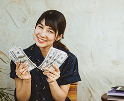 Woman holding cash in both hands and smilling