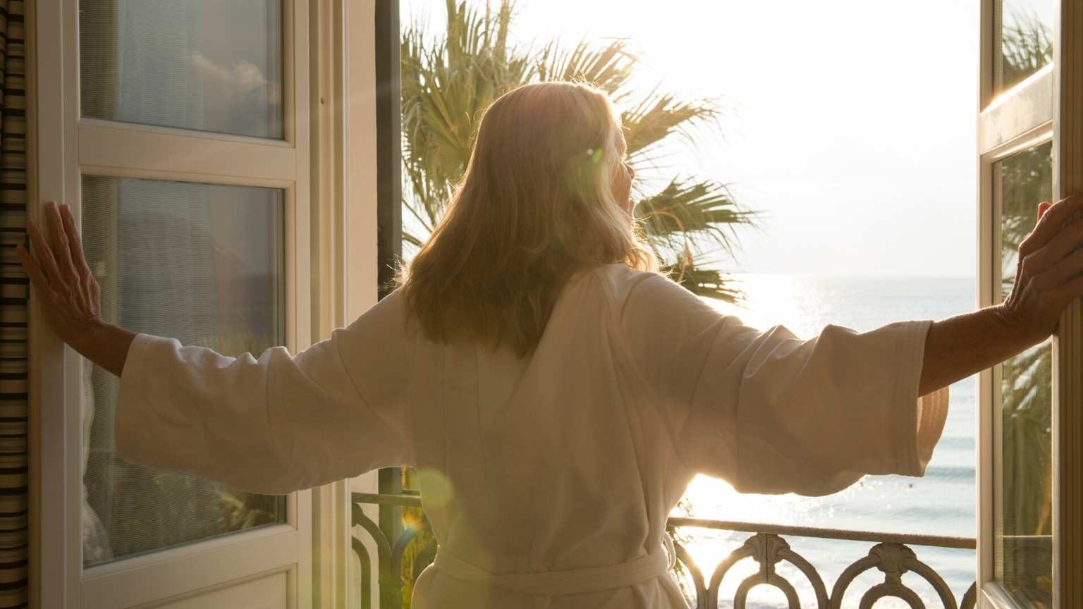 woman opening a window in a hotel