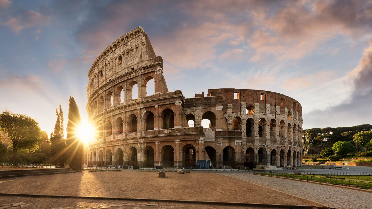 The Colosseum in Roma, Italy at sunset with the sun shining