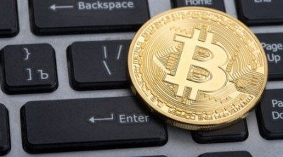 Golden coin with bitcoin logo on the middle over a keyboard