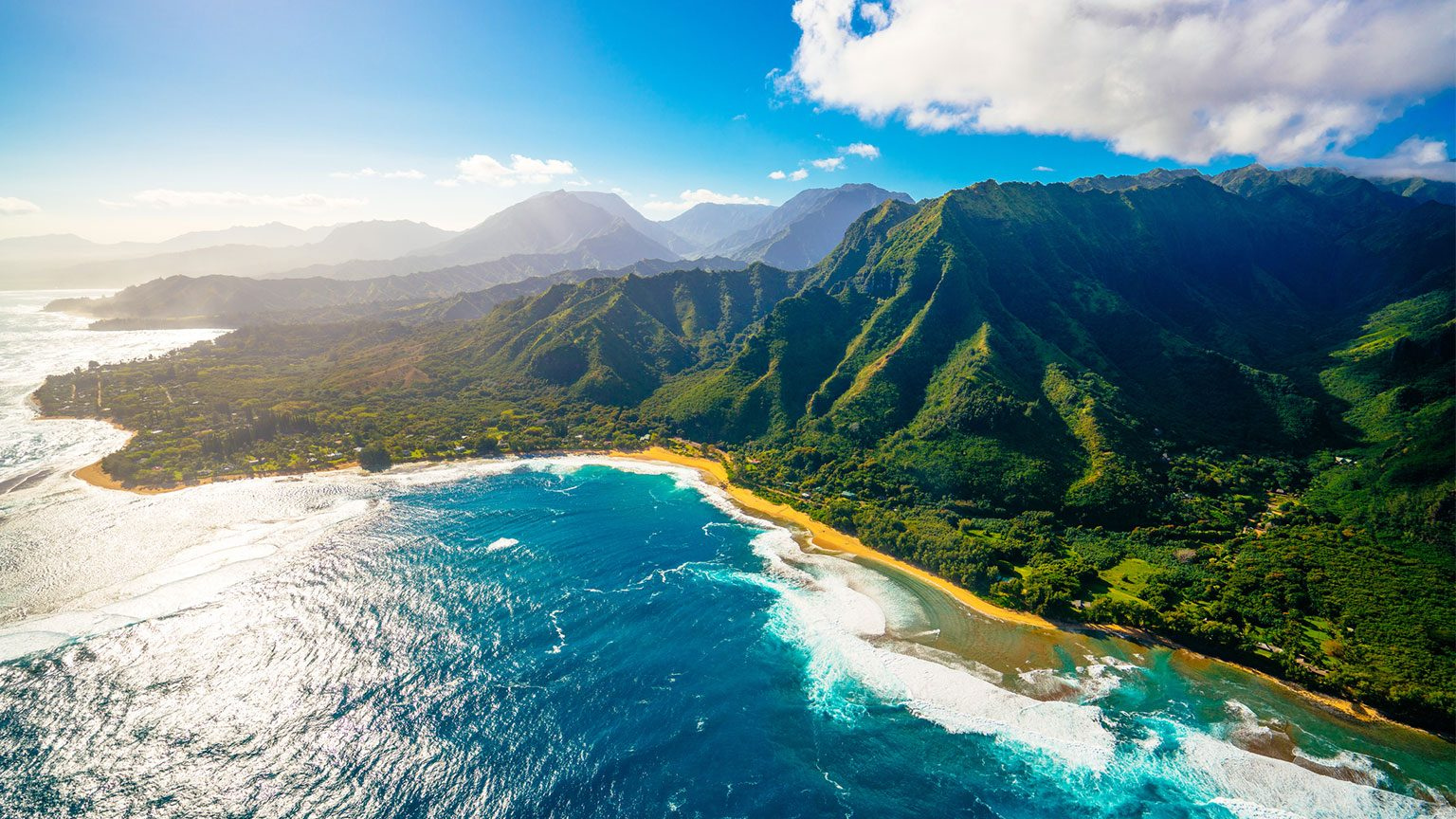 Aerial view of green Hawaiian island with blue sea in bright sun