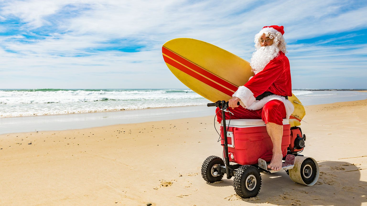 Santa Claus riding motorized cooler holding surfboard on beach