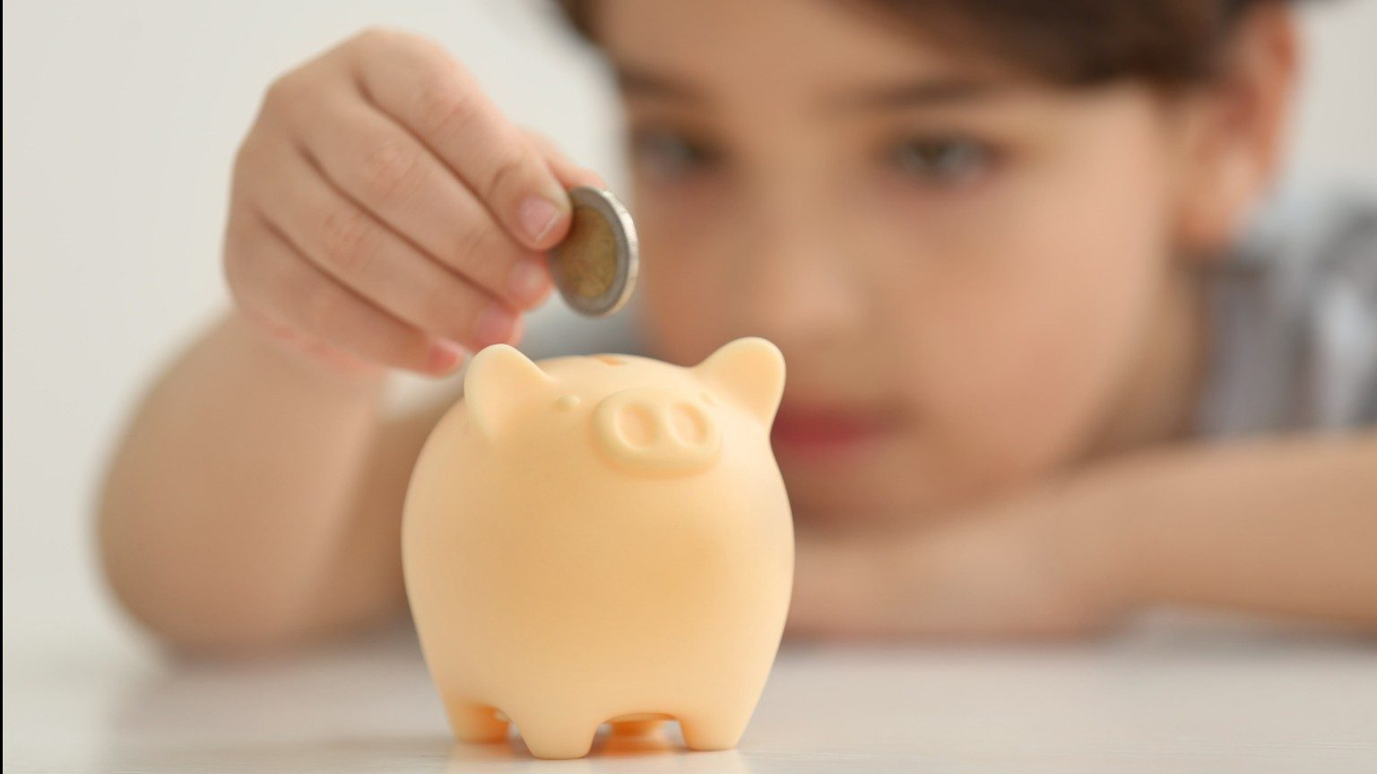 A child in the background dropping a coin in a piggy bank