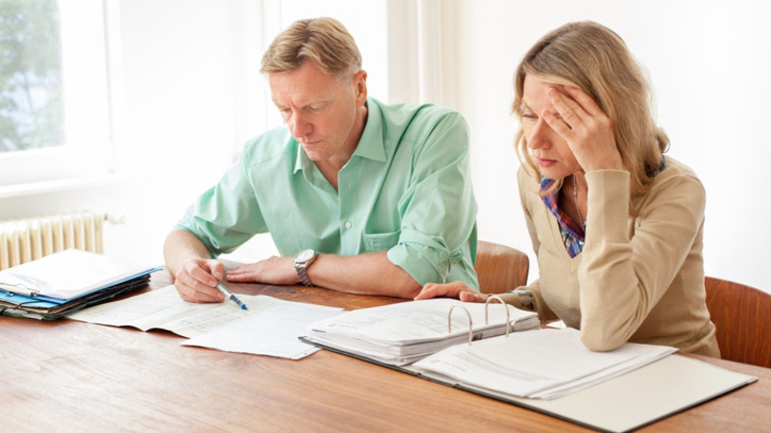 Couple looking stressed over paperwork and debt