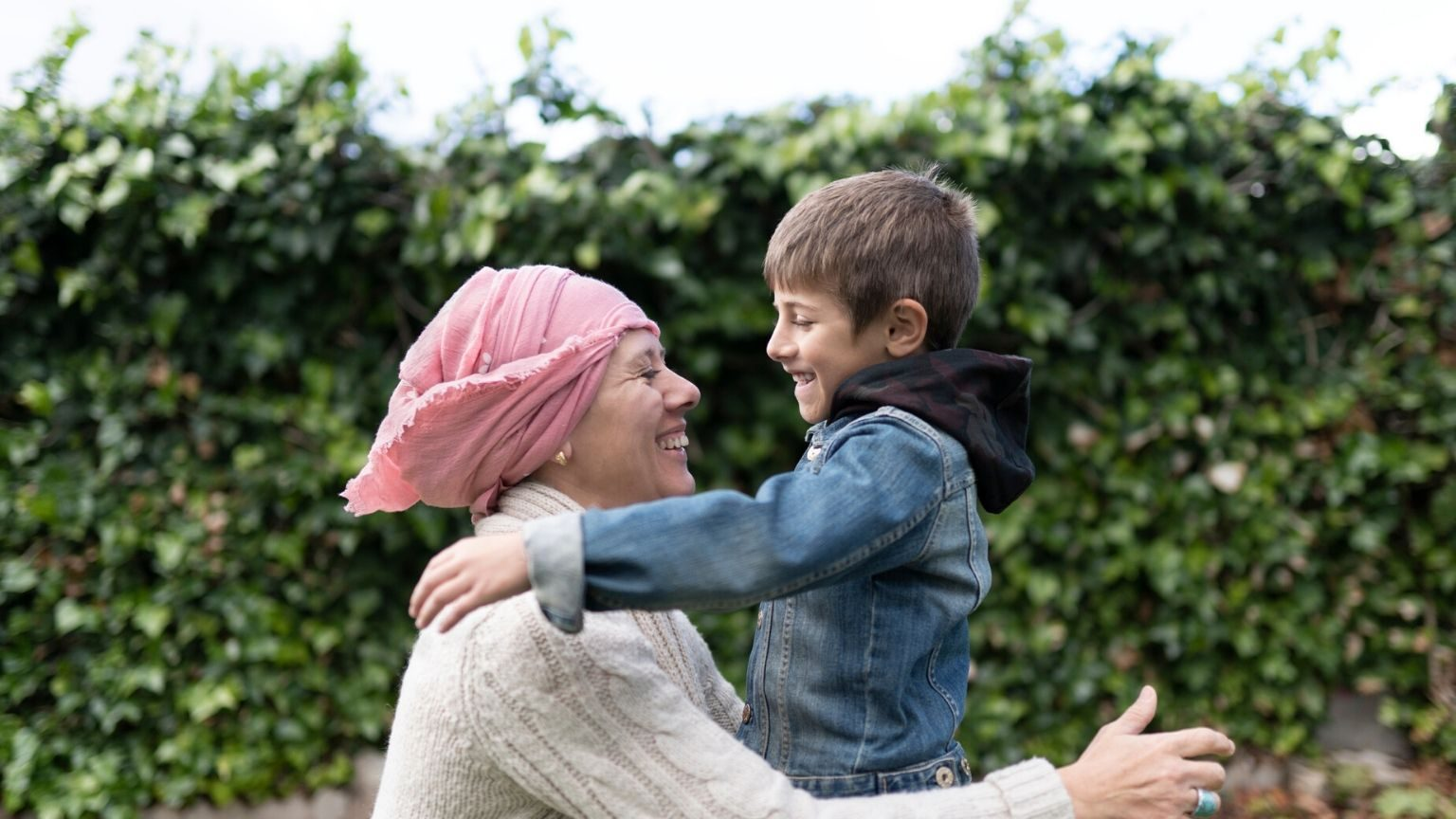Mother with cancer and her son with a pink scarf playing