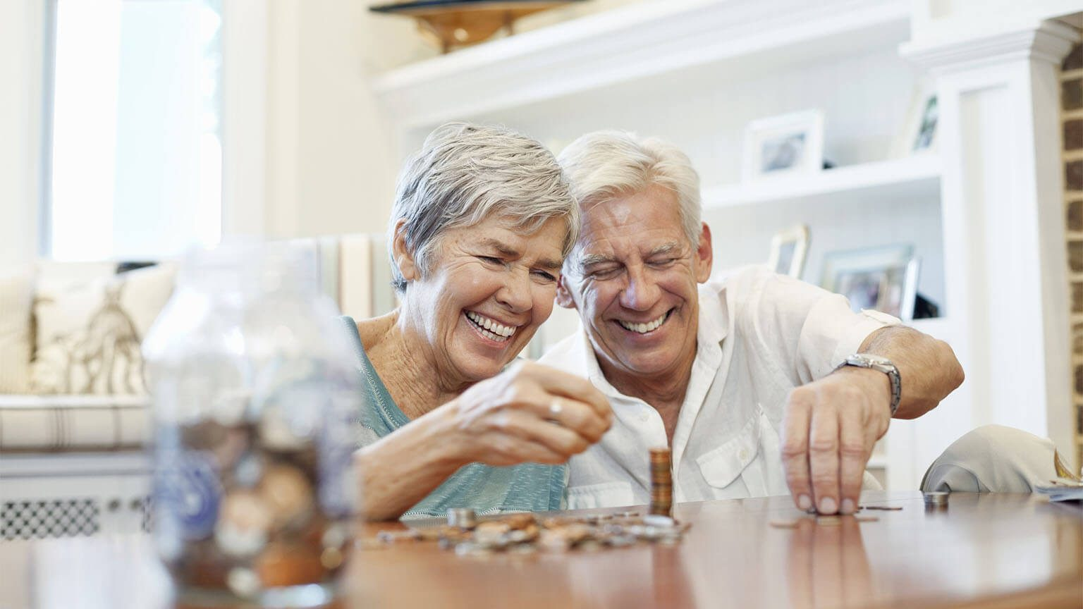 Senior couple counting coins at table