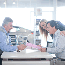 Car salesman and couple looking at contract in showroom