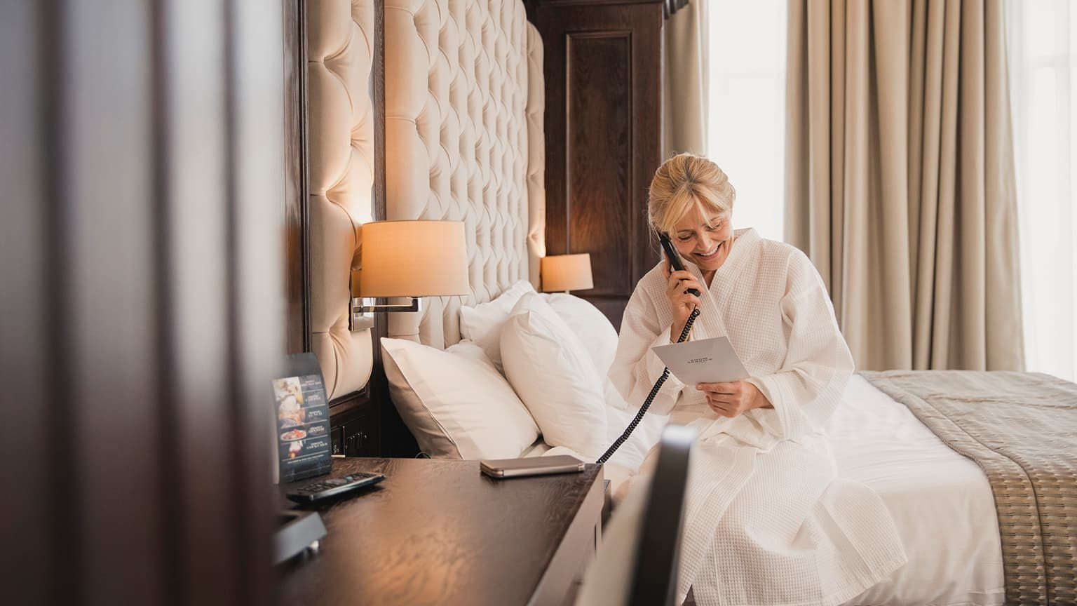 Mature woman is sitting on her bed in her hotel room