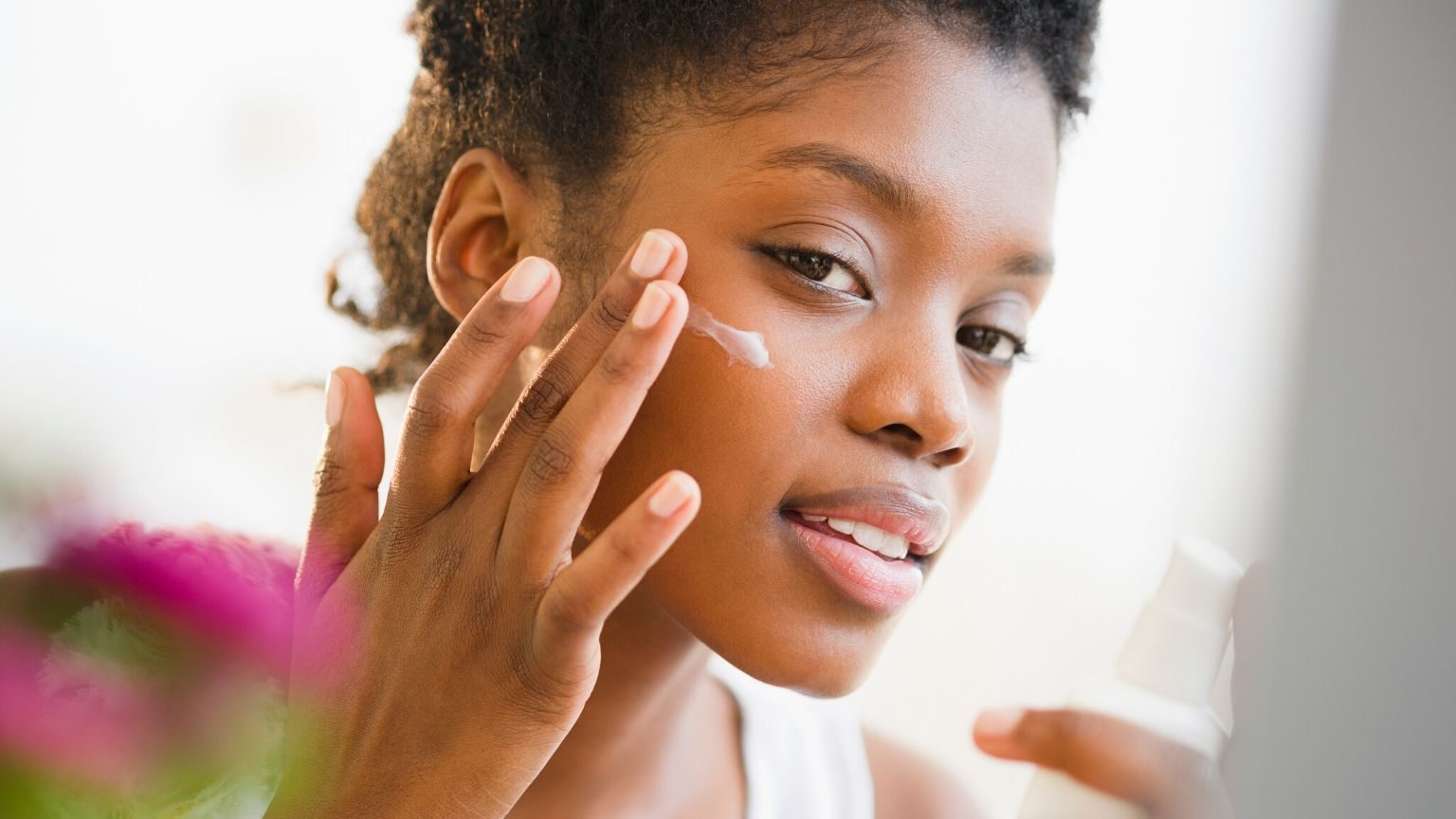 Woman using skincare product on face