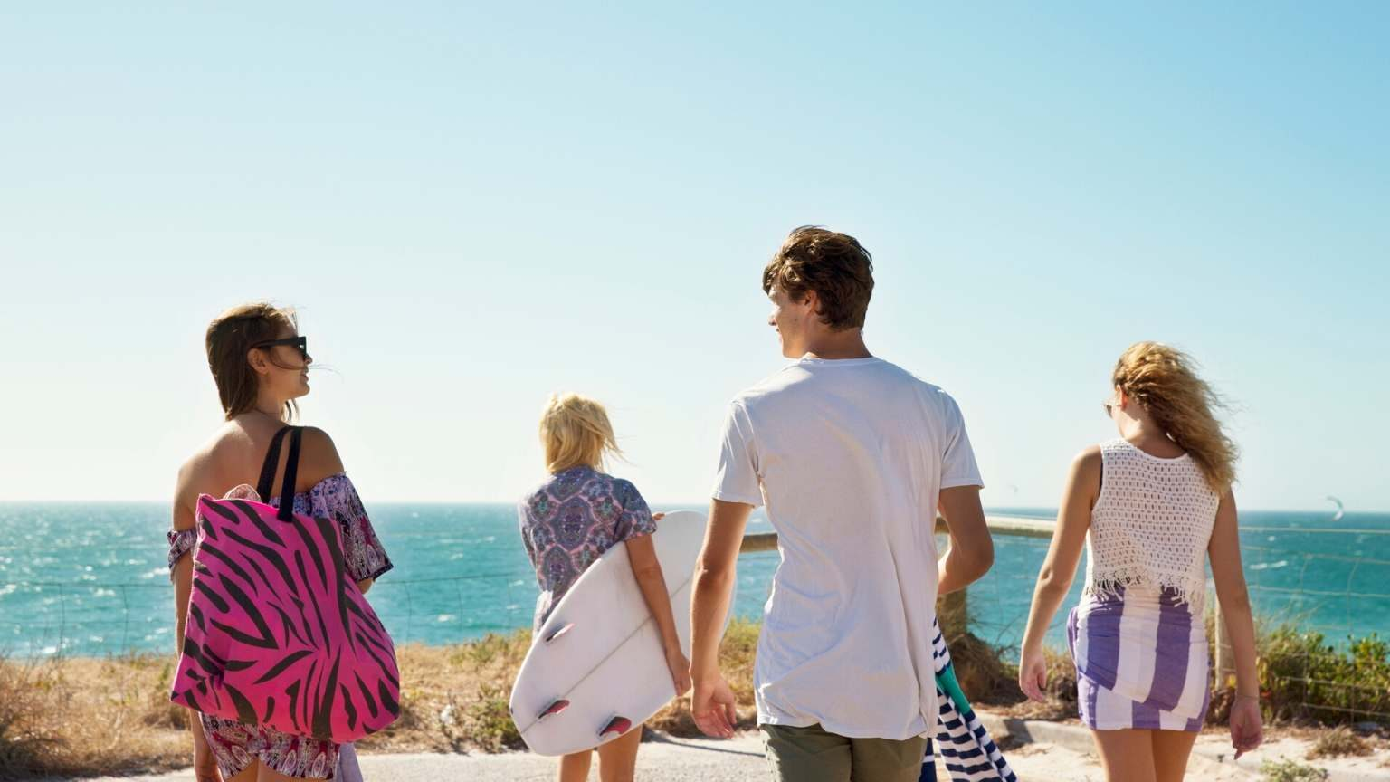 Young people walking to the sea to surf