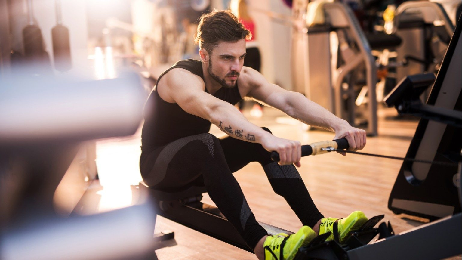 Determined man exercising on rowing machine in a gym