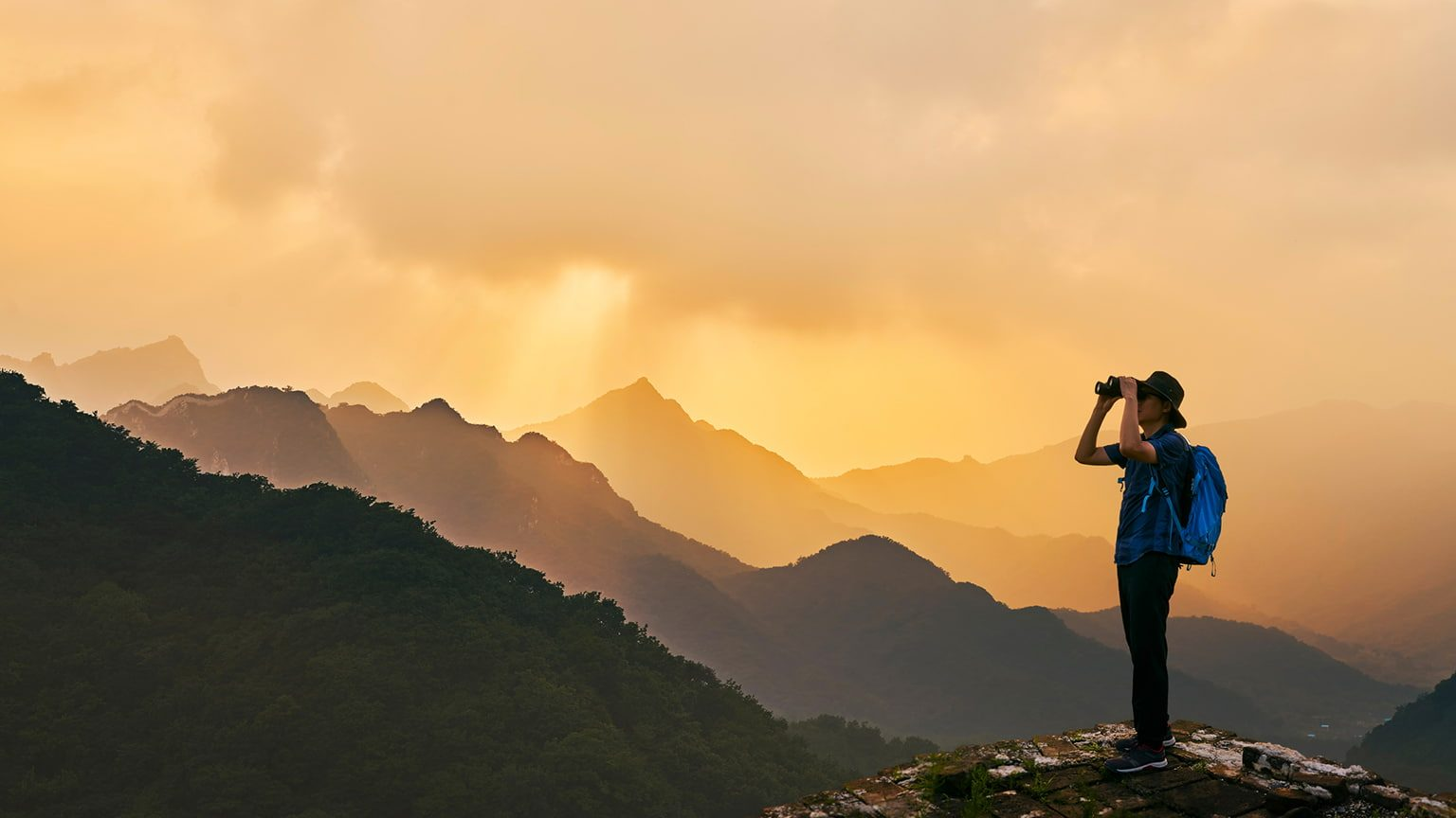 man on a mountain top with binocular