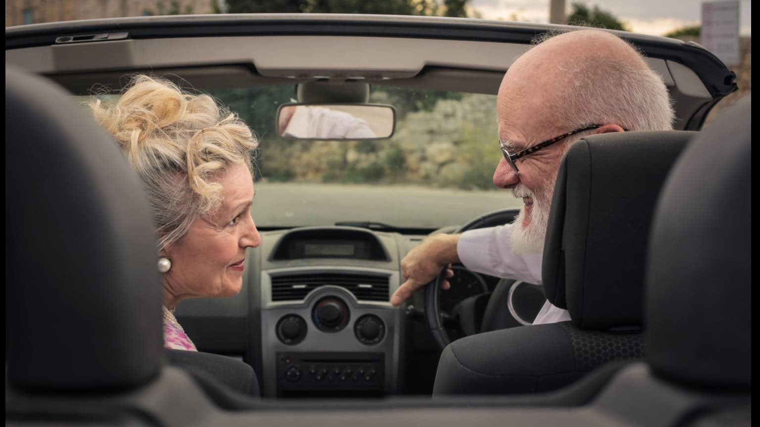 Happy elderly couple in a car