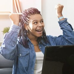 young woman cheering in front of laptop