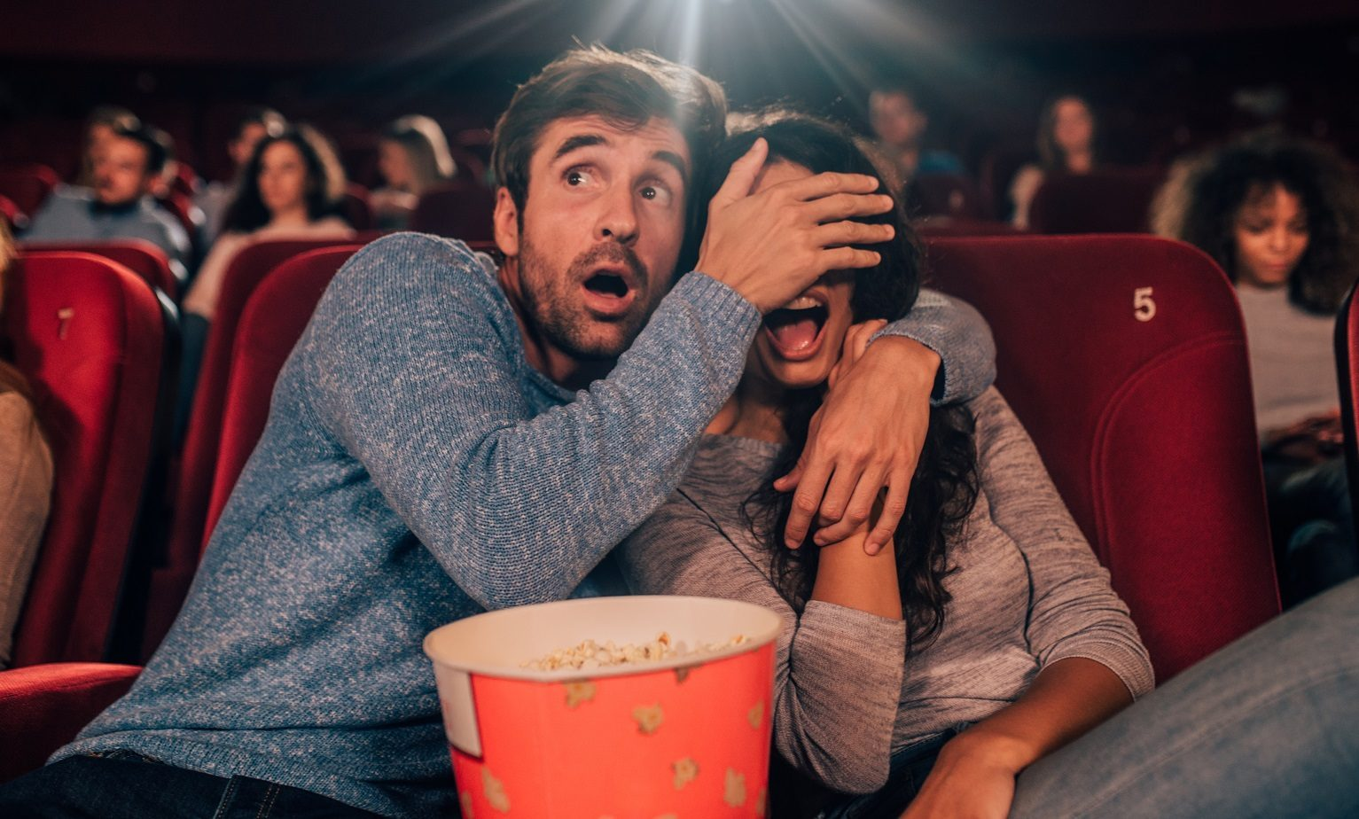 Scared couple watching horror movie at the cinema together