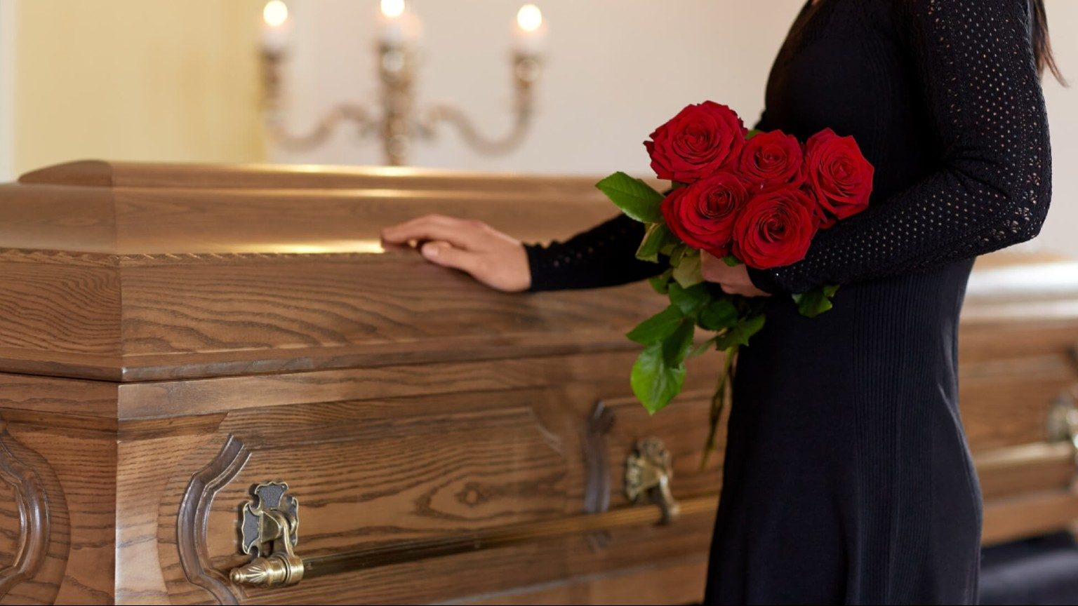Woman dressed in black with roses touching a coffin
