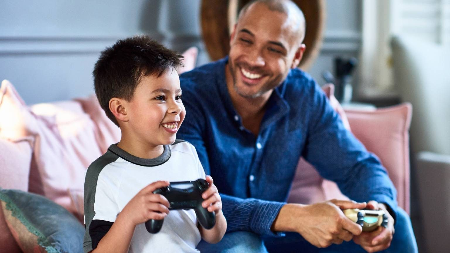 Cheerful father playing games console with son