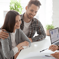 Couple smiling while other person explains contract